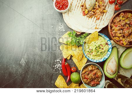 Mexican food mix: nachos, fajitas, tortilla, guacamole and salsa sauces and ingredients over black background. Top view with copy space