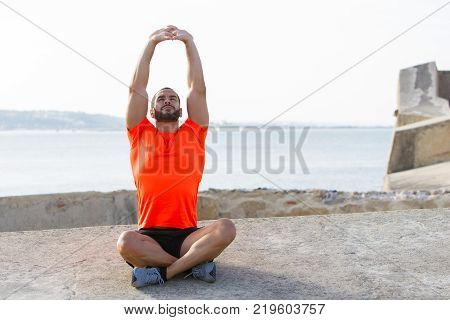 Portrait of serene young Latin American athlete wearing orange t-shirt sitting in lotus position and stretching or meditating on beach. Meditation and fitness concept