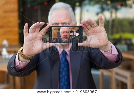 Closeup of anxious senior handsome man holding smartphone and taking selfie photo outdoors with focus on smartphone screen in foreground. Front view.