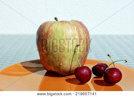 Closeup view of ripe apple and three sweet cherries with water drops on a orange plate against a high key background. Choose a focal point copy space for write.