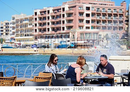 MARSALFORN, GOZO, MALTA - APRIL 3, 2017 - Family sitting at a restaurant table along the waterfront with the beach and town to the rear and waves crashing against the promenade wall Marsalforn Gozo Malta Europe, April 3, 2017.