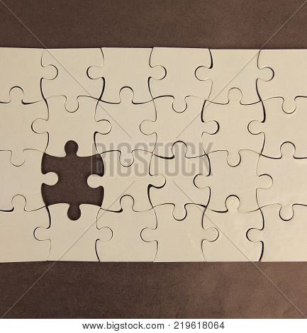 blank puzzle with missing piece, on a brown background.photo with copy space