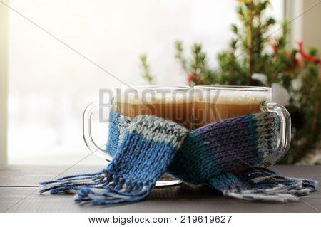 two mugs with frothy cappuccino in a blue scarf on the background of a festive Christmas tree by the window / together we meet the winter morning