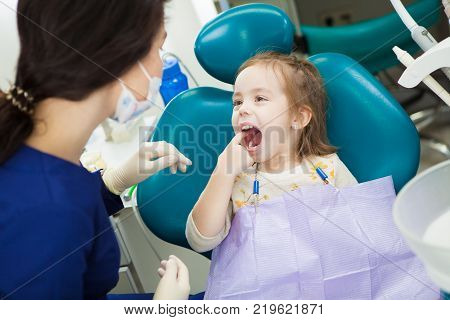Child at dentist office sits in comfortable chair with wide open mouth and finger in it. Kid shows to doctor in uniform and sterile rubber gloves where she has ache.