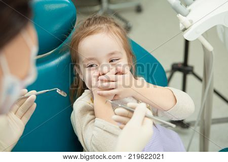 Kid afraid of procedure closes mouth with hands lies on dentist chair and doctor in sterile gloves holds special medical instruments for oral cavity examination.