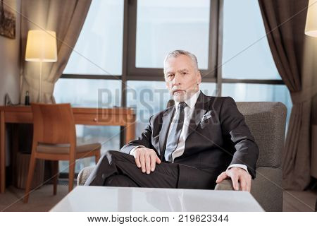Money calls. Handsome old  earnest man sitting in the chair while posing and looking straight