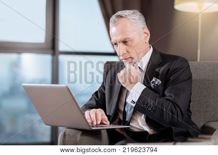 Business prospectives. Wistful senior focussed man staring at the screen while sitting and touching his chin