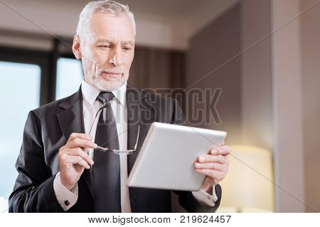 Working task. Senior inspired earnest man looking at the tablet while carrying it and concentrating