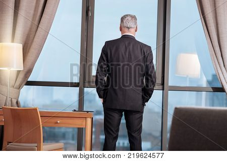 City view. Confident earnest senior man standing putting hands into the pocket while admiring view