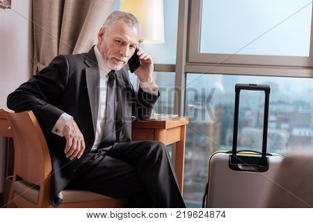 Profitable deal. Senior pleasant earnest man talking about business  while sitting and posing near the luggage