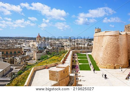 VICTORIA, GOZO, MALTA - APRIL 3, 2017 - Fortified buildings and landscaped gardens of the old moat within the citadel with views towards the city and Corpus Cristi Parish Church Victoria (Rabat) Gozo Malta Europe, April 3. 2017.