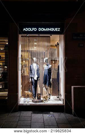 STRASBOURG FRANCE - DEC 23 2017: Adolfo Dominguez fashion shopping store window at night with male female mannequins wearing fashion luxury clothes