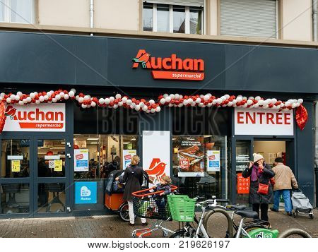 STRASBOURG FRANCE - DEC 4 2017: New Auchan Supermarket entrance in French neighborhood on a winter snow day with customers exiting the entrance of the store