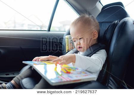 Cute little Asian 18 months / 1 year old toddler baby boy child sitting in car seat holding and enjoy reading book Happy traveling with child concept Little Traveler safety road trip concept