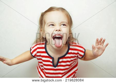 little girl shows her tongue in funny grimace with body leaned toward camera, dressed in striped T-shirt, and stands beside white wall emotional portrait photo.