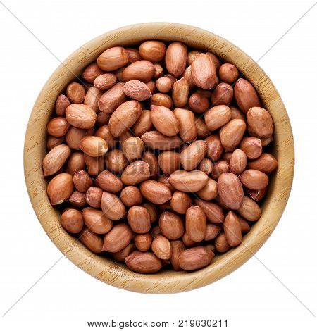 Peanuts in wooden bowl isolated on white top view.