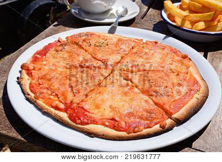 Cheese and tomato Margherita pizza on a wooden restaurant table Gozo Malta Europe.
