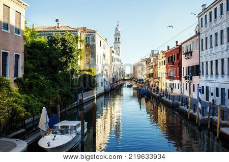 Boat moored between colorful houses. Canals in Venice, Italy.