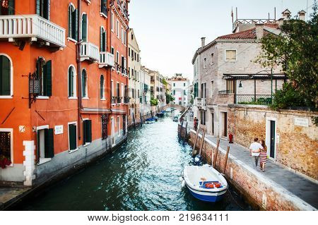 Boats moored between colorful houses and walking couples. Canals in Venice, Italy.