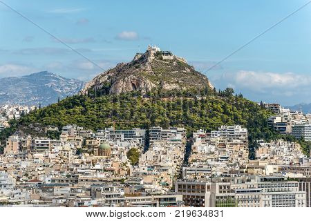 Athens Greece - November 1 2017: Cityscape of Athens and Lycabettus Hill also known as Lykabettos Lycabettos or Lykavittos. It is a Cretaceous limestone hill in Athens Greece.
