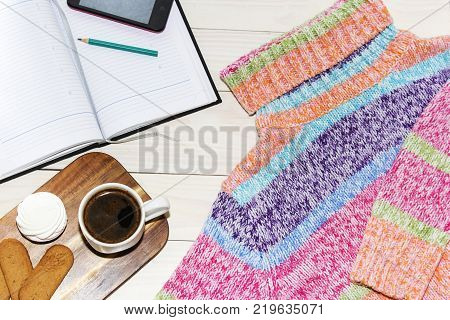 knitted sweater, coffee, laptop, smartphone top view Women's clothing