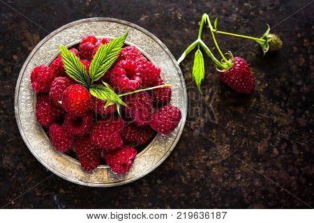 Raspberries. A Fresh Raspberry On A Silver Plate. Ripe Fresh Raspberries With Leaves On Rustic Backg