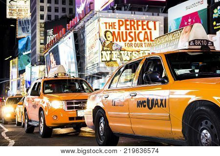 Times Square, New York City, New York, United States - circa 2015 -  line of taxi cabs driving in motion blurry times square night new york city with play marquees and brightly lit advertising signs