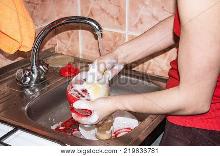 The girl washes the dishes in the sink