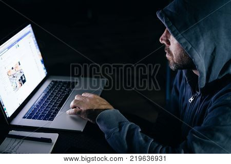 mysterious male hacker, hides his face under the hood, does something illegal on the laptop