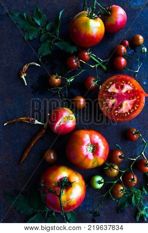 Top view colorful tomatoes red tomatoes yellow tomatoes orange tomatoes with water drops on the dark concrete background. Space for text selective focus.