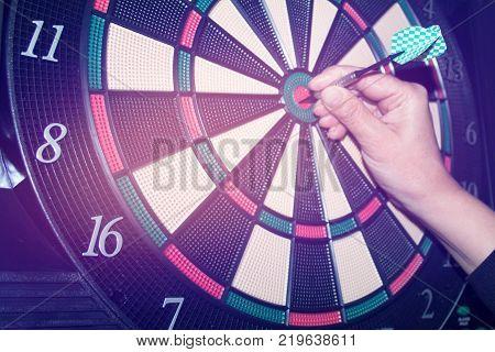 Success hitting target aim goal achievement concept background - three darts in bull's eye close up