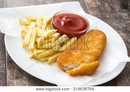 Close up traditional British fish and chips on wooden table.