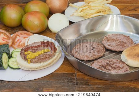 A hamburger on bread and vegetables, French fries and a pan with hamburgers