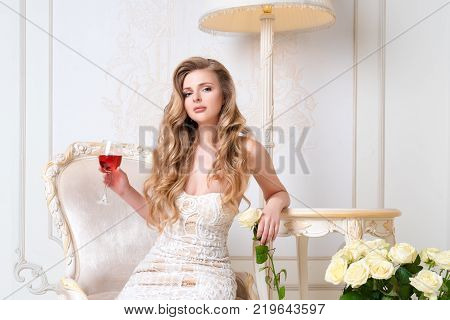Elegant blonde lady with glass of wine in restaurant. Beautiful sexy young woman with long hair perfect body and pretty face make-up wearing evening dress drinking alcohol in light luxury interior
