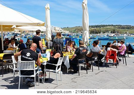 MARSAXLOKK, MALTA - APRIL 1, 2017 - Tourists relaxing at a pavement cafes along the waterfront with traditional Maltese fishing boats in the harbour and views towards the town Marsaxlokk Malta Europe, April 1, 2017.