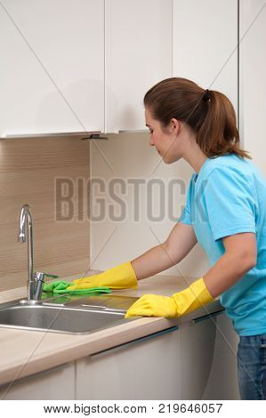 Charming young woman housewife  in rubber gloves -  wipes kitchen sink. Cleaning the kitchen