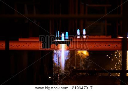 Iron factory with hot candent block of iron or steel or zinc in process of production or cooling