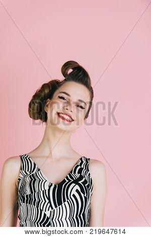 Makeup hairdresser and cosmetics. Woman with retro hair and fashionable makeup pinup. Beauty and fashion cosmetics. Girl in stylish vintage dress on pink background. pinup youth and look.