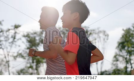 low angle view fo Chinese man & son jogging outdoors in garden back lighted