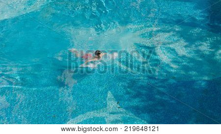 high angle view of Asian teenager swimming outdoors in blue pool