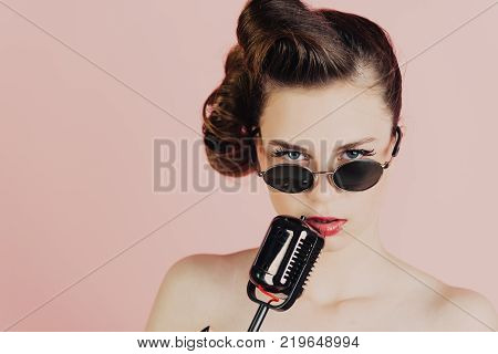Music look and retro style pinup. Beauty and vintage fashion. Woman singer with stylish retro hair and makeup. Girl in glasses sing in microphone. Pin up young girl on pink background radio.