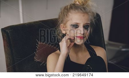 Young teenage girl actress with smudged makeup smiles after stop crying becuase of loss film casting sits in chair in studio indoors