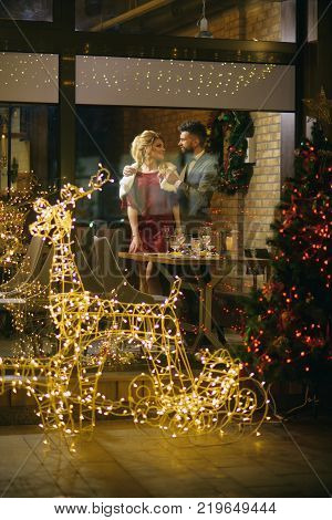 Happy family celebrate new year and christmas. Woman and man in restaurant with festive decorations. Couple in love enjoy xmas cuisine food wine. Winter season romance. Holidays celebration concept.
