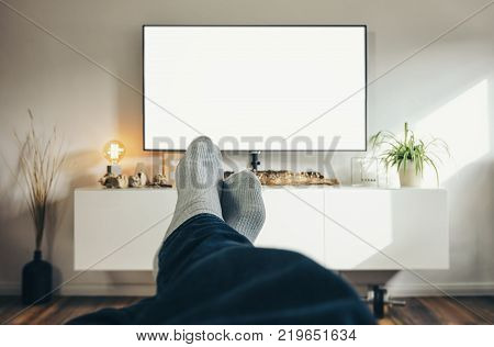 POV-Shot from a young watching tv with his feets and socks at home including copy space. ideal for websites and magazines layouts