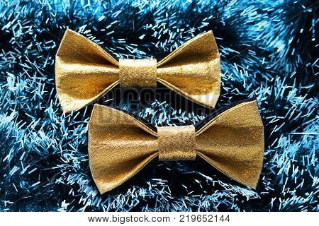 two festive gold butterfly bow tie against a background of green Christmas tree tinsel.