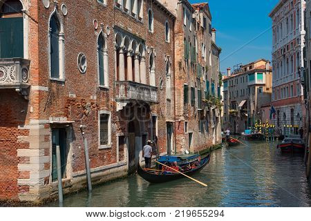 VENICE, ITALY - MAY 23, 2017: Traditional narrow canal street with gondolas and old houses in Venice, Italy. Architecture and landmarks of Venice. Beautiful Venice postcard.