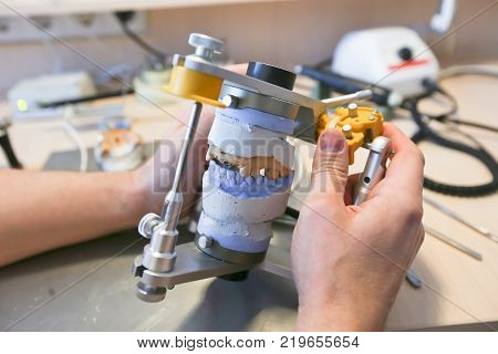 The master makes dental crowns for dentistry. Manufacture of dental crowns.