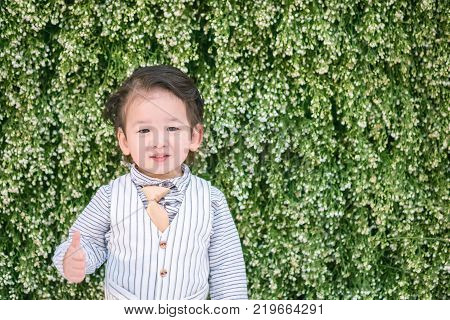 Closeup happy asian kid with admire motion on plant backdrop wedding textured background with copy space
