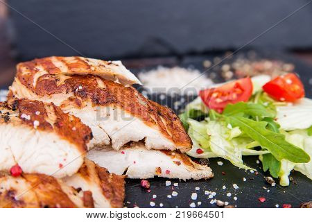 Close up delicious grilled turkey fillet served wit vegetable salad and spices on wooden board