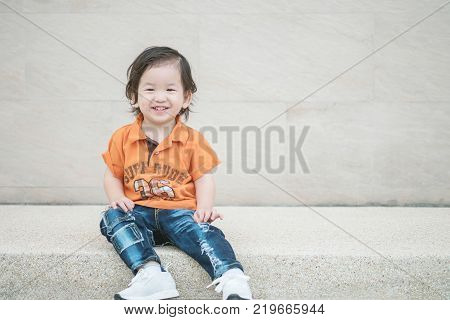 Closeup happy asian kid with smile face sit on marble stone floor and wall textured background with copy space